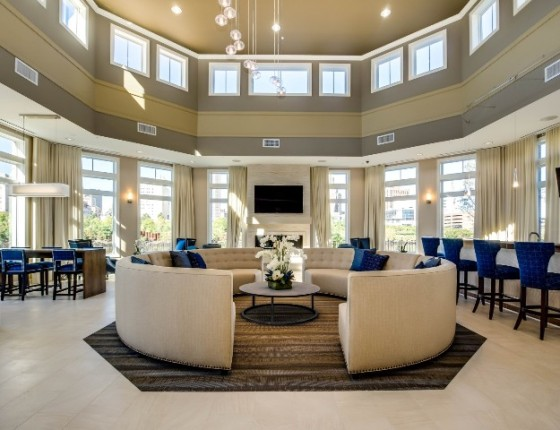 The residents' lounge at Water's Edge is one of the community's many indoor and outdoor amenity spaces, featuring a bar, flat screen television, fireplace and riverfront views.
